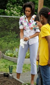 Michelle Obama gloves up to work along side elementary school garden helpers